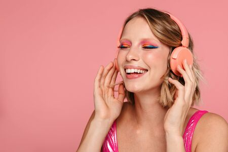 Photo pour Portrait of a pretty smiling young girl with bright makeup wearing summer clothing standing isolated over pink background, listening to music with wireless headphones - image libre de droit
