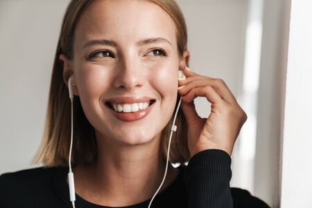 Photo pour Attractive smiling young blonde short haired woman leaning on a wall while standing indoors, listening to music with earphones - image libre de droit