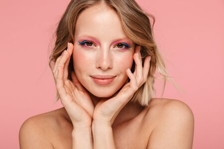 Foto de Beauty portrait of an attractive smiling young topless blonde haired woman standing isolated over pink background, posing - Imagen libre de derechos