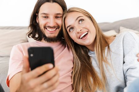 Photo for Image of a smiling dreaming young loving couple on sofa indoors at home using mobile phone. - Royalty Free Image