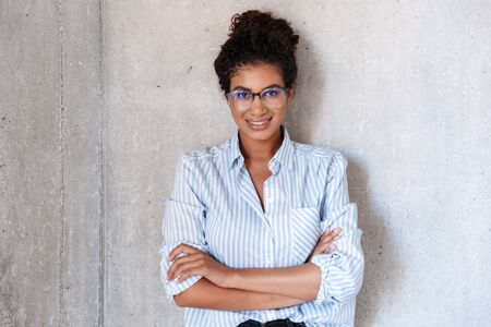 Photo pour Beautiful smiling young african woman wearing casual clothes and glasses leaning on a wall indoors, posing while standing, arms folded - image libre de droit