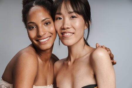 Photo pour Two multiethnic young beautiful smiling women standing isolated over gray background, hugging - image libre de droit