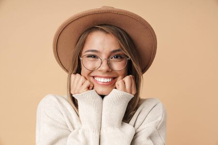 Photo pour Portrait of excited young woman in hat smiling and looking at camera isolated over beige background - image libre de droit