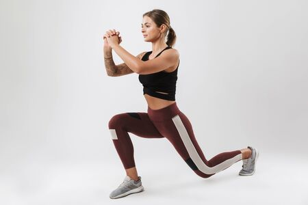 Foto für Photo of pretty woman in sportswear stretching her body while doing workout isolated over white background - Lizenzfreies Bild