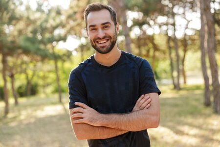 Photo pour Image of a young strong happy cheery sports man posing outdoors in nature green park looking camera. - image libre de droit