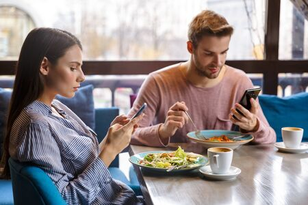 Photo pour Attractive young couple having lunch at the cafe indoors, having a meal, using mobile phone - image libre de droit