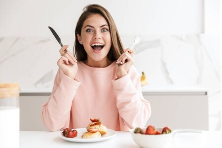 Photo pour Beautiful smiling young girl having tasty healthy breakfast while sitting at the kitchen table - image libre de droit