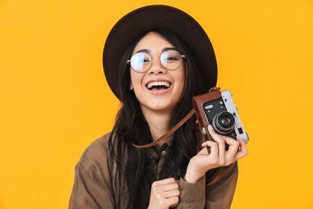 Foto de Image of young brunette asian tourist woman wearing hat using retro camera isolated over yellow background - Imagen libre de derechos