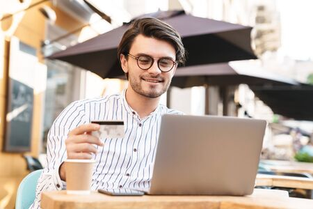 Photo pour Photo of smiling young man wearing eyeglasses using laptop and holding credit card while drinking coffee in cafe outdoors - image libre de droit