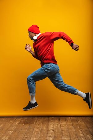Foto de Full length side view portrait of an attractive confident casual young african man running over yellow background - Imagen libre de derechos
