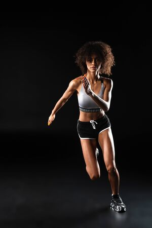 Foto für Image of focused african american sportswoman doing exercise while working out isolated over black background - Lizenzfreies Bild