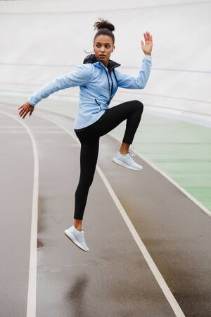 Photo for Beautiful young fit african sportswoman wearing wireless earphones doing stretching exercises at the stadium, jumping - Royalty Free Image