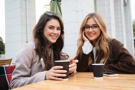 Photo pour Two cheerful attractive women friends sitting at the cafe outdoors, drinking coffee - image libre de droit