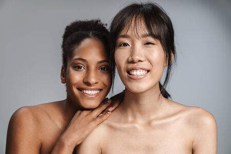 Photo for Portrait of two multinational half-naked women smiling and looking at camera isolated over grey background - Royalty Free Image