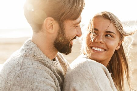 Photo pour Close up of a smiling beautiful young couple embracing while standing at the beach - image libre de droit
