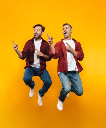 Photo for Full length image of two handsome men 30s in red shirts smiling and pointing fingers at copyspace isolated over yellow background - Royalty Free Image