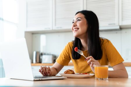 Photo pour Image of a beautiful positive cheerful brunette young woman at the kitchen indoors at home using laptop computer have a dinner. - image libre de droit