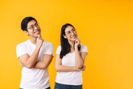 Foto de Portrait of a beautiful cheerful pensive young asian couple wearing casual clothing standing isolated over yellow background, looking away - Imagen libre de derechos