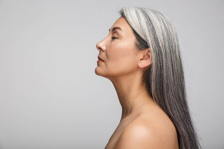 Foto de Side view beauty portrait of an attractive sensual mature topless woman with long gray hair standing isolated over gray background, eyes closed - Imagen libre de derechos