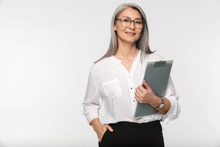 Photo pour Portrait of an attractive smiling mature businesswoman in formal wear standing isolated over white background, holding a clipboard - image libre de droit