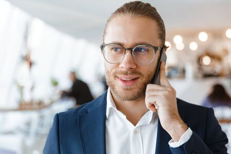 Photo pour Image of pleased young businessman indoors in office talking by mobile phone. - image libre de droit