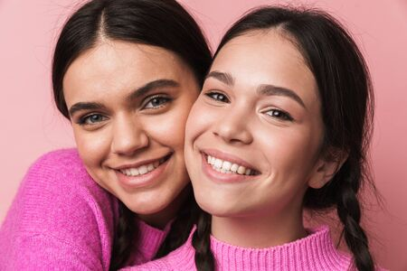 Photo pour Two cheerful cute teenage girls having fun isolated over pink background, grimacing, hugging - image libre de droit