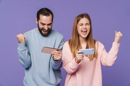 Foto de Image of excited emotional loving couple isolated over purple background play games by mobile phones make winner gesture. - Imagen libre de derechos