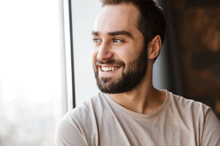 Photo pour Handsome smiling young bearded man standing at the window at home, looking away - image libre de droit