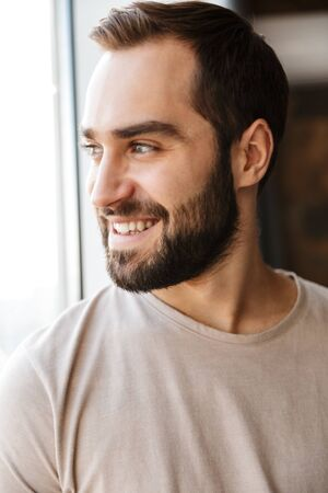 Photo for Handsome smiling young bearded man standing at the window at home, looking away - Royalty Free Image