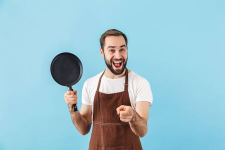 Photo pour Excited young bearded man cook wearing apron standing isolated over blue background, showing frying pan, pointing finger - image libre de droit