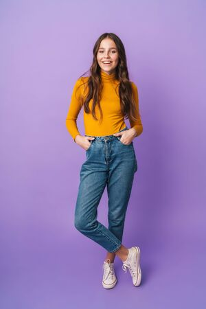 Photo pour Full length image of young beautiful woman with long brown hair smiling and posing at camera isolated over violet background - image libre de droit