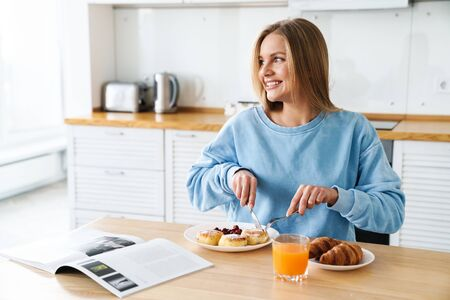 Photo pour Image of cheerful young woman with blonde hair reading magazine while having breakfast at modern kitchen - image libre de droit