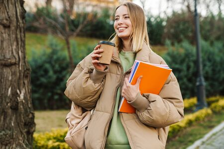 Photo for Portrait of smiling young woman holding exercise books and drinking coffee takeaway while walking in park - Royalty Free Image