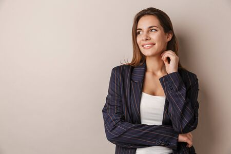 Photo for Photo of joyful businesswoman in formal suit smiling and looking aside isolated over white background - Royalty Free Image