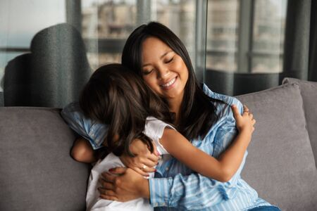 Photo for Photo of pleased pregnant asian woman with her little daughter hugging and smiling while sitting on couch at home - Royalty Free Image