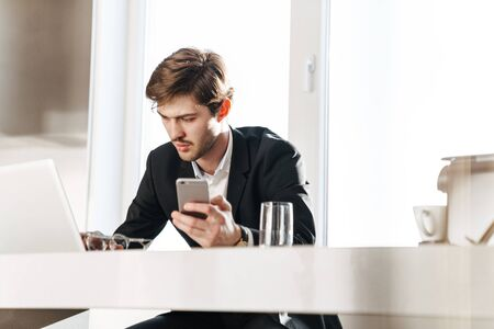 Photo pour Photo of concentrated businessman wearing black suit working with laptop and cellphone at modern kitchen - image libre de droit