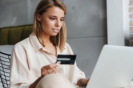 Photo pour Image of focused nice woman in pajamas holding credit card and using laptop while sitting on armchair at living room - image libre de droit