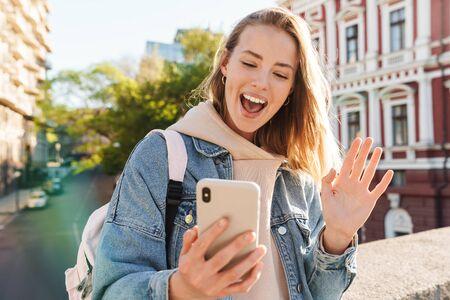 Photo pour Beautiful cheerful young blonde woman wearing denim jacket walking in the city, taking a selfie, waving - image libre de droit