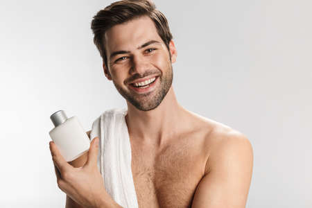 Photo pour Photo of happy half-naked man with cosmetic clay mask on his face and towel smiling at camera isolated over white background - image libre de droit