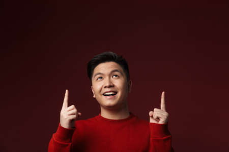 Photo for Image of happy young asian man smiling and pointing fingers upward isolated over burgundy background - Royalty Free Image
