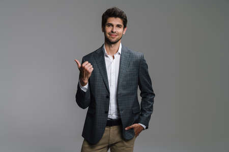 Photo pour Photo of cheerful businessman in jacket smiling and pointing finger aside isolated over grey wall - image libre de droit