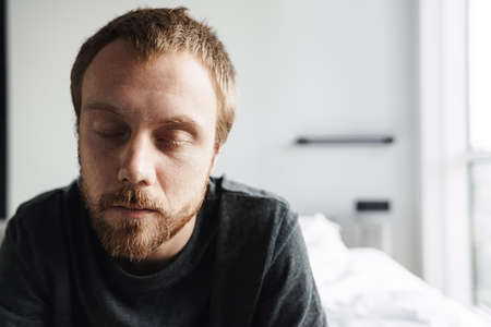 Photo pour Photo closeup of sleepy redhead man posing with eyes closed while sitting on bed at bright room - image libre de droit
