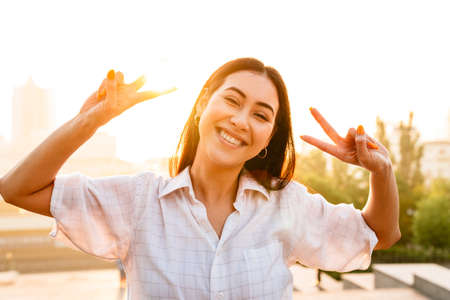 Photo pour Photo of joyful beautiful asian woman laughing and gesturing peace sign while walking outdoors - image libre de droit