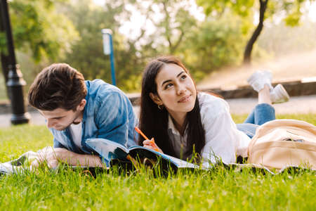 Photo for Image of joyful multicultural student couple doing homework and smiling while lying on grass in park - Royalty Free Image