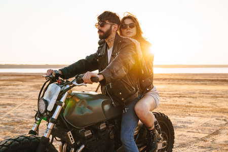 Photo pour Beautiful young stylish couple enjoying ride on a motorbike at the beach - image libre de droit