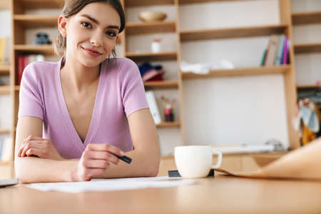 Photo of young smiling woman making sketches while drinking coffee at table in bright office