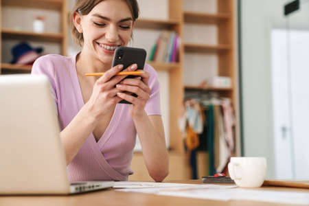 Photo of young smiling woman using cellphone while working with laptop at table in office