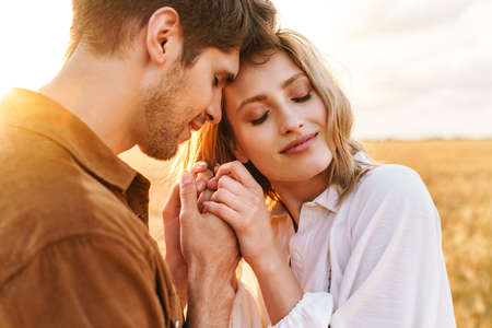 Photo for Image of young caucasian beautiful couple hugging together in golden field on countryside - Royalty Free Image