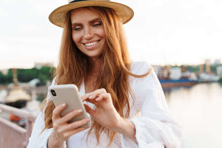 Photo pour Image of joyful ginger woman smiling and using mobile phone while walking on promenade - image libre de droit