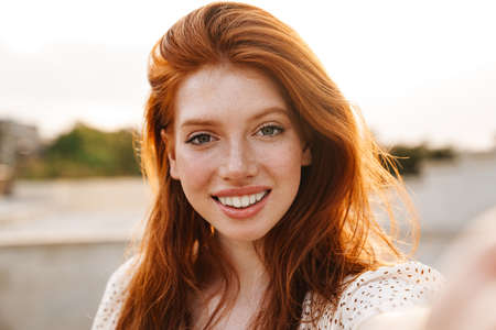 Photo pour Image of cheerful ginger girl taking selfie and smiling at camera at city street - image libre de droit